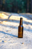 A brown beer bottle on a sandy road royalty free stock images