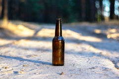 A brown beer bottle on a sandy road Stock Image