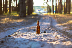 A brown beer bottle on a sandy road royalty free stock image