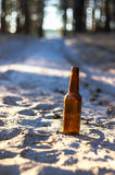 A brown beer bottle on a sandy road Stock Images