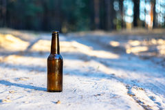 A brown beer bottle on a sandy road Stock Photos