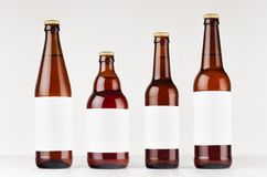 Brown beer bottles collection different type with blank white label on white wooden board, mock up. Royalty Free Stock Image