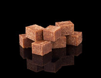 Brown beet sugar cubes on black background. With reflection Stock Photography