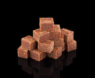 Brown beet sugar cubes on black background Royalty Free Stock Image