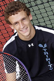 Brown-behaarter junger Mann, der mit Tennisschläger lächelt Stockbild