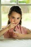 Brown-behaartes Kind, das Joghurt isst Lizenzfreies Stockbild