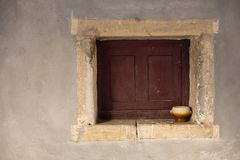 Brown and beige bowl on a closed window royalty free stock images