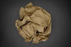 Brown and beige crumpled paper ball. Isolated on black background royalty free stock photos