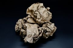 Brown and beige crumpled paper ball. Isolated on black background royalty free stock image