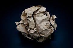 Brown and beige crumpled paper ball. Isolated on black background stock photography