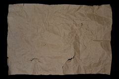Brown and beige crumpled paper, cardboard. Isolated on black background stock images