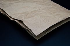 Brown and beige crumpled paper, cardboard. Isolated on black background royalty free stock images