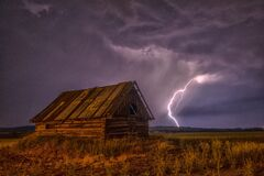 Brown and Beige Wooden Barn Surrounded With Brown Grasses Under Thunderclouds Stock Photography