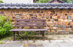 Brown bench against retro japanese style brick wall Stock Images