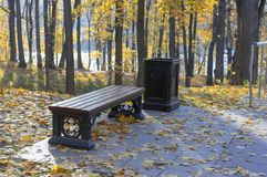 Brown bench in the autumn city park royalty free stock photos