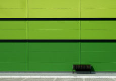 Brown bench in front of green wall Royalty Free Stock Images