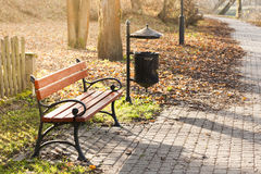 Brown bench in a park. Royalty Free Stock Photos