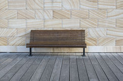 Brown bench on wooden deck with sandstones wall background Stock Photo