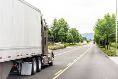 Brown big rig long haul semi truck transporting commercial cargo in semi trailer running on the divided road. Brown commercial grade freight transportation stock photo