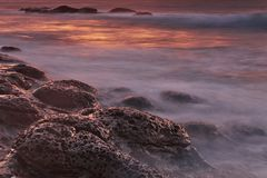 Brown and Black Rock Formations With Fog during Sunset Royalty Free Stock Photos