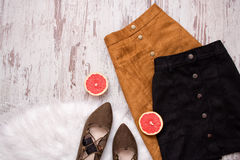 Brown and black suede skirt, brown suede shoes, cut grapefruit halves. Wooden background. Fashion concept. top view Royalty Free Stock Images