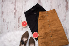 Brown and black suede skirt, brown suede shoes, cut grapefruit halves. Wooden background. Fashion concept Royalty Free Stock Images