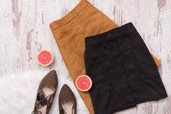 Brown and black suede skirt, brown shoes, cut grapefruit halves.Fashion concept Royalty Free Stock Images