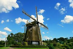 Brown and Black Windmill Under Cumulus Clouds Surrounded by Green Leaf Trees Stock Image