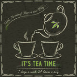 Brown blackboard with  two cup of hot tea and teapot Royalty Free Stock Images