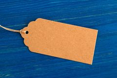Brown blank paper price tag or label set on the blue wooden background. stock photo