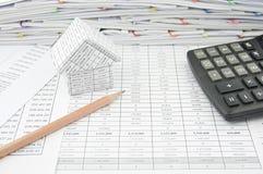 Brown-Bleistift nahe Haus und Taschenrechner auf Finanzkonto Lizenzfreie Stockfotos