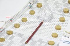 Brown-Bleistiftpunkt zum Haus zwischen Stapel von Goldmünzen Stockbild