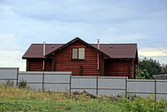 Brown-Blockhaus hinter einem Eisenzaun Lizenzfreies Stockbild