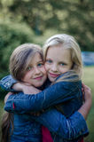 Brown and blond haired cute little girls friends smiling and hug. Stock Image