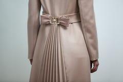 Brown-Bogen ziehen an sich vom braunen Mantel der Frauen zurück Lizenzfreie Stockbilder