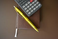 Brown book diary with a gray calculator and a yellow pen on a brown matte background. Excellent bright photos for stores for articles and magazines and any royalty free stock images