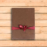 Brown book gift. With red ribbon and bow. On a wooden table.  Royalty Free Stock Photography