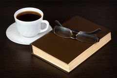 Brown book with glasses on a table Stock Images