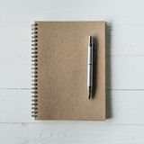 Brown book and pen on wood table Royalty Free Stock Photography