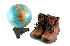 Brown boot next to a rotating globe royalty free stock photography