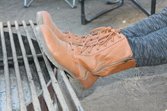 Brown Boots. With gray leggings set up on the edge of the firepit stock photography