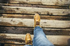 Brown boots steps on wooden plank. Wet wooden plank and brown boots steps jeans of the person Royalty Free Stock Image