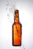 Brown bottle of beer and a water splash Stock Photo