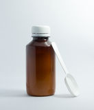 Brown bottle of cough syrup with white plastic spoon Stock Photos
