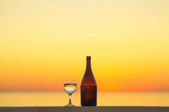 Brown bottle and glass of white vine with reflections of houses Royalty Free Stock Photos