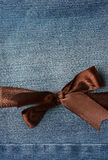 Brown bow on jeans. Brown bow on blue jeans textile texture background Royalty Free Stock Photo