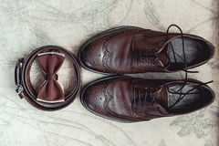 Brown bow tie, leather shoes and belt. Grooms wedding morning. Close up of modern man accessories Royalty Free Stock Photo