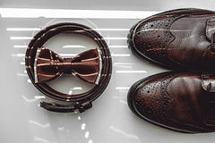 Brown bow tie, leather shoes and belt. Grooms wedding morning. Close up of modern man accessories Royalty Free Stock Images