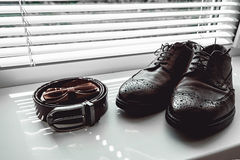 Brown bow tie, leather shoes and belt. Grooms wedding morning. Close up of modern man accessories Royalty Free Stock Image