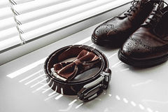 Brown bow tie, leather shoes and belt. Grooms wedding morning. Close up of modern man accessories Stock Photo